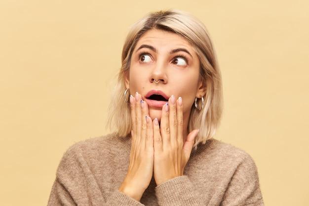 Verrassing en verbazing concept. foto van mooie jonge vrouw met blond bob kapsel mond wijd openen en ogen wijd open, geschokt door onverwacht nieuws, hand in hand op haar wangen