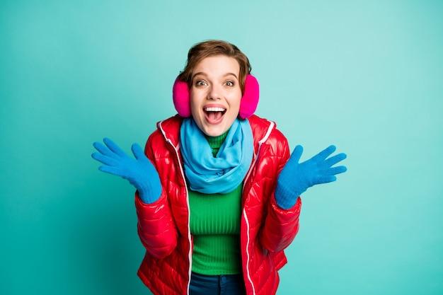 Verrassing! foto van grappige dame handen omhoog houden waardoor ouders kerstbezoek dragen casual rode overjas blauwe sjaal roze oorbeschermers groene trui geïsoleerde wintertaling kleur muur