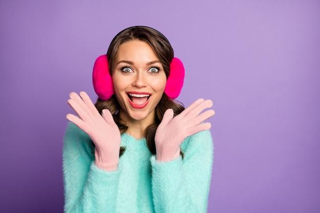 Verrassing! portret van grappige mooie dame hand in hand opgeheven onverwachte kerst ouders bezoeken dragen casual fuzzy sweater roze oorwarmers pastel handschoenen.