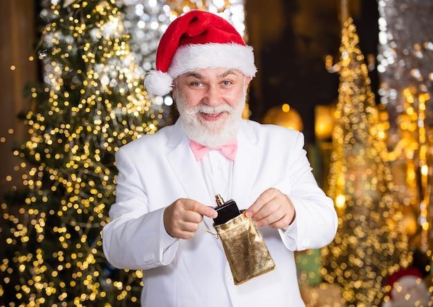 Verrassing. santa zakenman heeft keulen aanwezig. elite dure geur. nieuwjaarscadeau voor mannen. parfumerie. schoonheid en mensen concept. gelukkig man met parfum verlichte achtergrond.