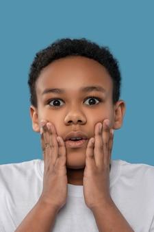 Verrassing, schok. geschokte zwarte jongen van basisschoolleeftijd die zijn wangen aanraakt met handpalmen terwijl hij in de studiofoto is