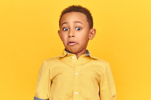 Verrassing, verbazing en shock concept. geïsoleerd beeld van geschokt verbaasd afro-amerikaans jongetje dat een oprechte verbaasde reactie uitdrukt, grimassen terwijl hij naar iets walgelijks kijkt