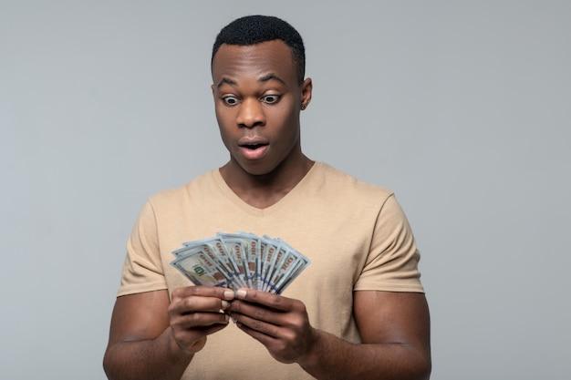 Verrassing. verrast vrolijke jonge volwassen donkere man met grote ogen kijken naar bankbiljetten in handen
