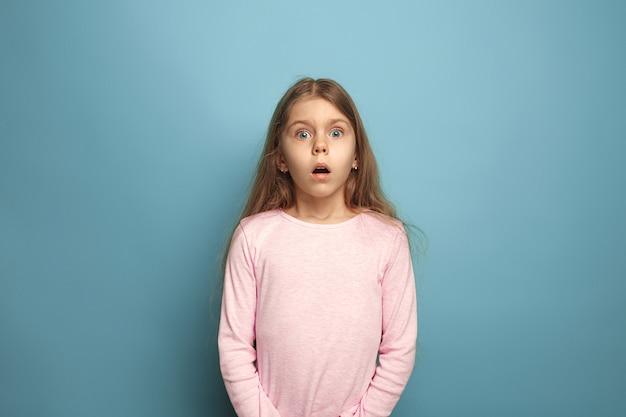 Verrassing, verrukking. verrast tienermeisje op blauw. gezichtsuitdrukkingen en mensen emoties concept