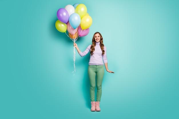 Verrassing! volledige lengte foto van vrij grappige dame brengen veel kleurrijke lucht ballonnen vrienden evenement feestkleding lila trui groene broek laarzen geïsoleerde blauwgroen pastelkleur
