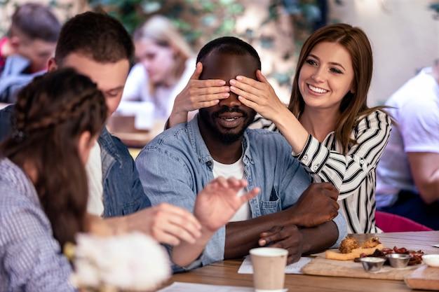 Verrassing voor een afrikaanse jongen van beste vrienden in het gezellige plaatselijke café met heerlijk eten