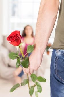 Verrassing voor haar. bijgesneden afbeelding van man met een rode roos terwijl zijn vriendin op de achtergrond zit
