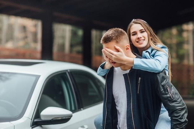 Verrassing voor man, vrouw in de buurt van witte auto.