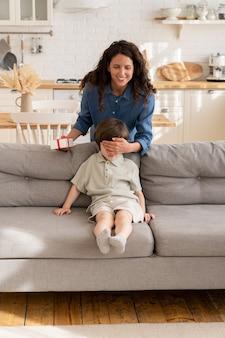 Verrassingscadeau voor zoontje, moeder sluit de ogen van de jongen die op de bank zit, feliciteer het kind met verjaardag