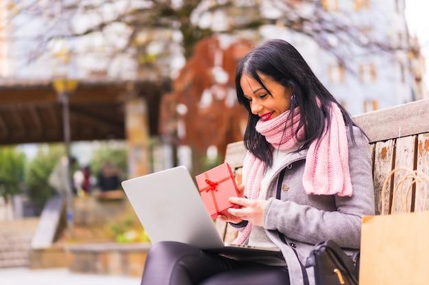 Verrassingsgeschenk, kaukasisch donkerbruin meisje dat het geschenk van de vriend opent in een videogesprek met de computer, gescheiden door afstand