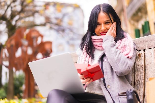 Verrassingsgeschenk, portret van zeer opgewonden meisje dat het geschenk van de vriend opent in een videogesprek met de computer, gescheiden door afstand