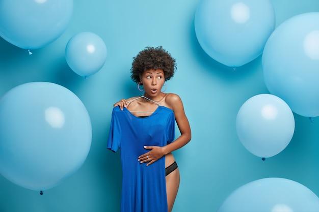 Verrast afro-amerikaanse vrouw kiest jurk uit haar garderobe, kiest outfit om te dragen bij speciale gelegenheden, staat uitgekleed en verbergt halfnaakt lichaam als iemand komt, geïsoleerd over blauwe muur