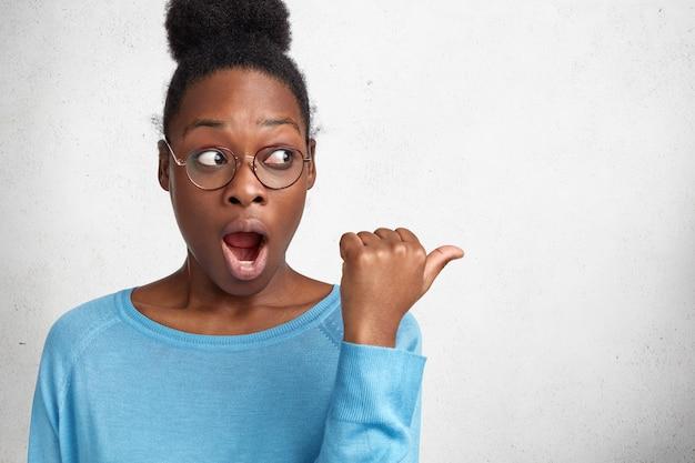 Verrast afro-amerikaanse vrouw met donkere huid, draagt casual trui en bril, geeft met duim aan op lege kopie ruimte