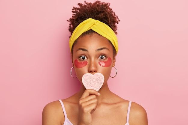 Verrast afro-vrouwelijk model past cosmetische pads toe voor wallen, houdt de spons op de mond, heeft een frisse, zachte huid, heeft wijd geopende ogen, staat binnen