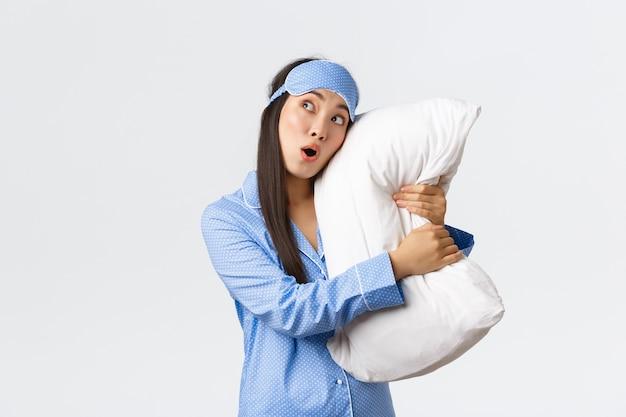 Verrast aziatisch meisje met ontzag dat slaapmasker en pyjama draagt terwijl ze in bed ligt en kussen knuffelt, geschrokken kijkt in de linkerbovenhoek, kaak laat vallen en zeg wauw onder de indruk, staande witte muur