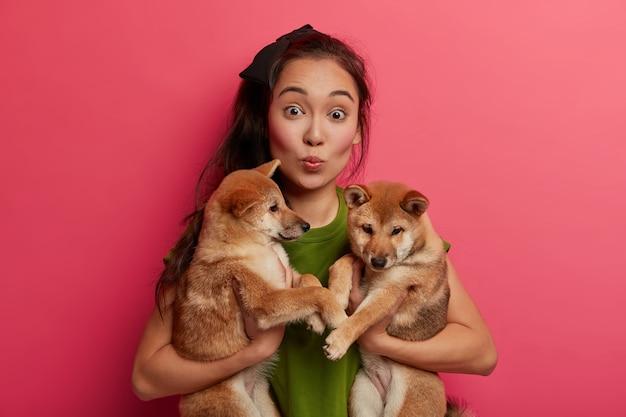 Verrast aziatische dame houdt lippen gevouwen, poseert met twee puppy's, draagt naar dierenartskliniek.