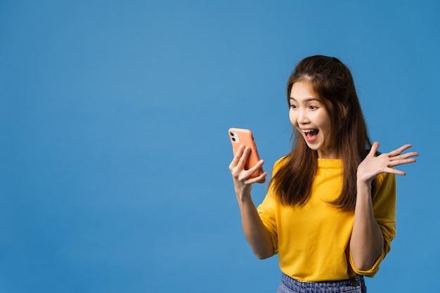 Verrast aziatische jongedame met behulp van mobiele telefoon met een positieve uitdrukking, glimlacht breed, gekleed in casual kleding en staande geïsoleerd op blauwe achtergrond. gelukkige schattige blije vrouw verheugt zich over succes.