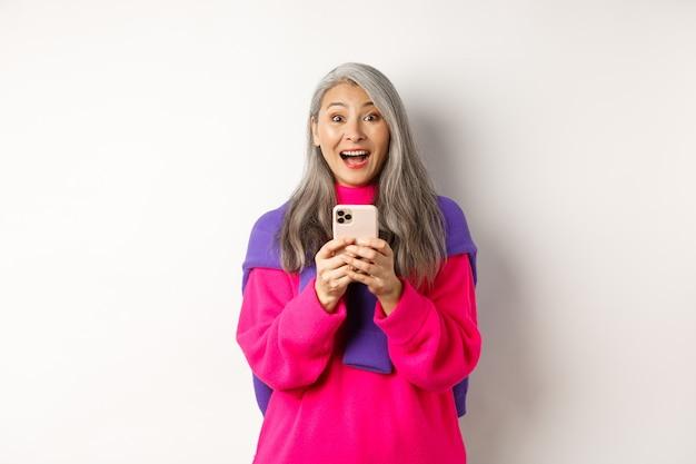Verrast aziatische vrouw die lacht naar de camera na het lezen van promotie op smartphone, staande met mobiele telefoon op witte achtergrond