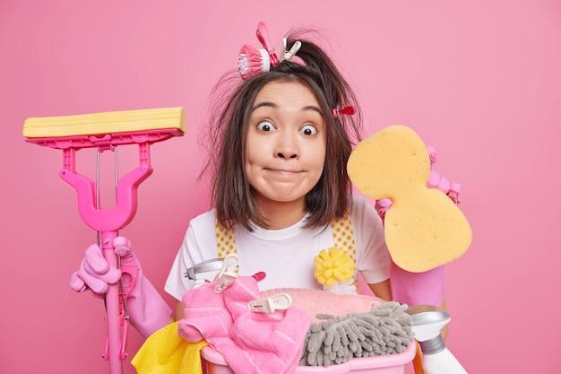 Verrast aziatische vrouw houdt spons gebruikt schoonmaakbenodigdheden poses met dweil bezig met huishoudelijk werk in nieuwe huishoudingen tegen roze achtergrond. huishoudelijke taken, wastijd en huishoudconcept