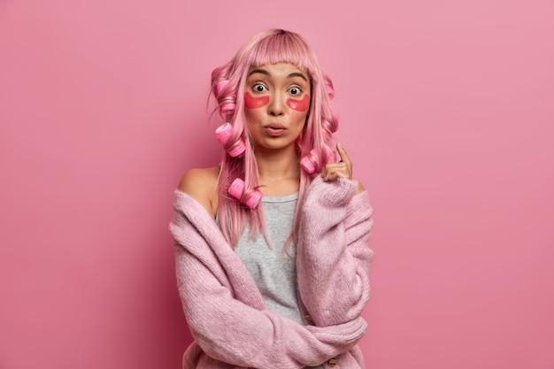 Verrast aziatische vrouw met roze haar, past krulspelden, collageenpleisters toe tijdens de ochtendspits, ondergaat schoonheidsbehandelingen