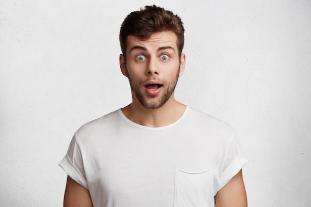 Verrast bebaarde jonge man met afgeluisterde blauwe ogen, gekleed in een casual wit t-shirt