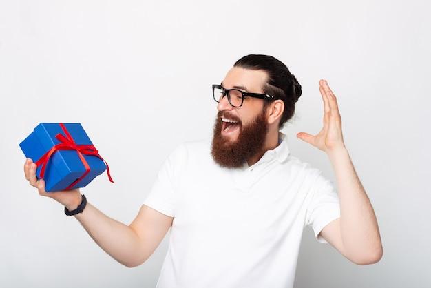 Verrast bebaarde man houdt een geschenkdoos op een witte achtergrond.