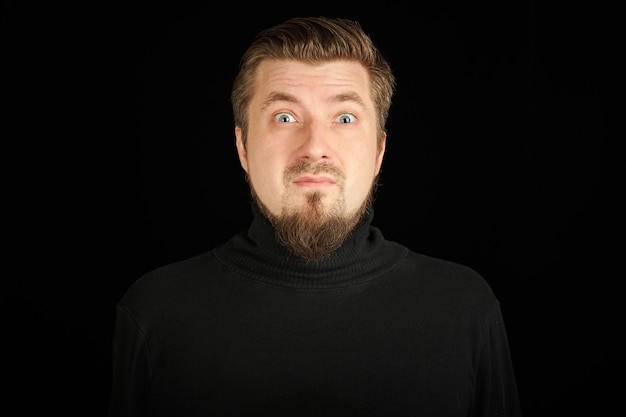 Verrast bebaarde man, zwarte achtergrond. jonge kerel in zwarte polohals trui. grappige en eigenaardige man.