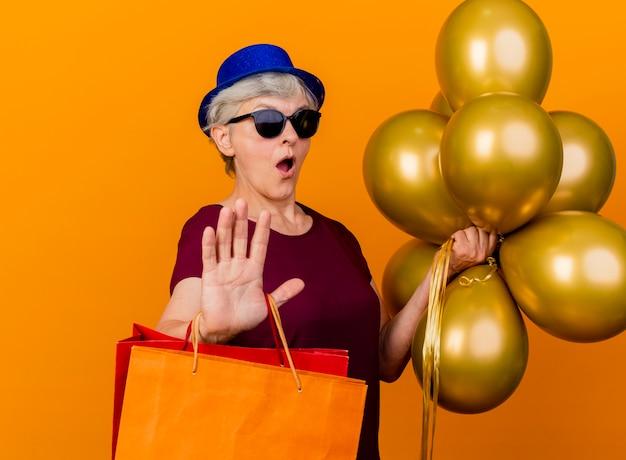 Verrast bejaarde vrouw in zonnebril met feestmuts houdt helium ballonnen en papieren boodschappentassen gebaren stophand teken geïsoleerd op oranje muur met kopie ruimte