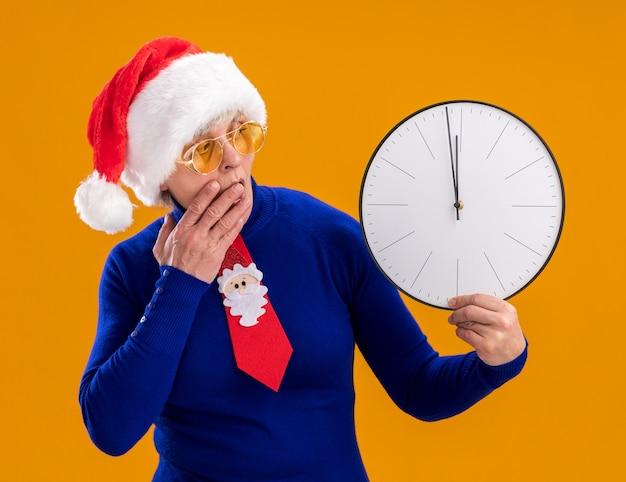 Verrast bejaarde vrouw in zonnebril met kerstmuts en santa stropdas houden en kijken naar klok geïsoleerd op oranje muur met kopie ruimte