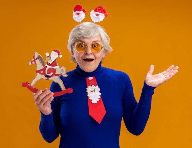 Verrast bejaarde vrouw in zonnebril met santa hoofdband en santa stropdas santa houden op hobbelpaard decoratie en hand open houden geïsoleerd op een oranje achtergrond met kopie ruimte