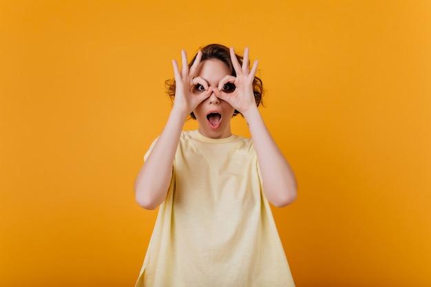 Verrast blank meisje in oversized t-shirt gek rond terwijl poseren voor foto. binnenportret van prachtige verfijnde vrouw die gekke bekken trekt.
