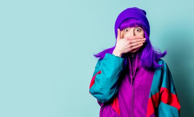 Verrast blank meisje met paars haar en trainingspak bedekt haar mond op blauwe muur