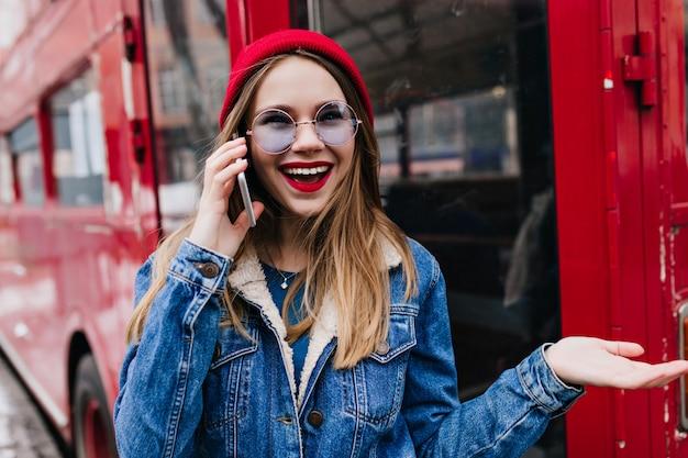 Verrast blanke vrouw in rode hoed praten over de telefoon.