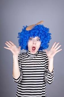 Verrast blauw haarmeisje met vastgelopen kam.