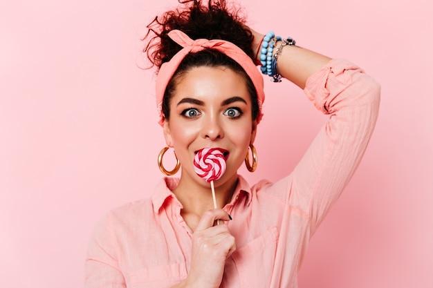 Verrast blauwogige brunette meisje in roze pin-up outfit eet lolly op geïsoleerde ruimte.