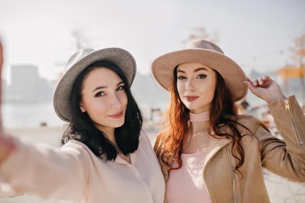 Verrast bleke vrouw met gemberhaar poseren met brunette jonge vrouw in koude dag