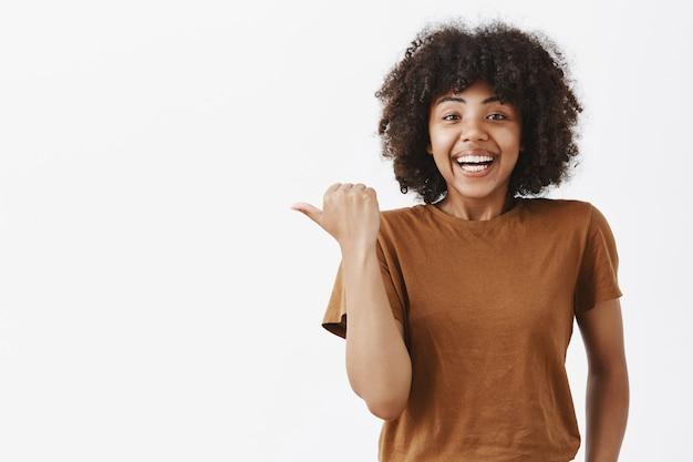 Verrast blij en onder de indruk blij aantrekkelijk donkerhuidige vrouw in bruin t-shirt met krullend haar wijzend naar links met duim en glimlachend uitleggend wat er geweldig is gebeurd