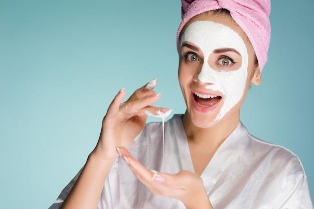 Verrast blij meisje met een roze handdoek op haar hoofd zet een wit voedzaam masker op haar gezicht
