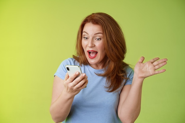 Verrast blij van middelbare leeftijd mooie roodharige vrouw kijk smartphone hand opsteken feestelijke opwinding open mond reageren onder de indruk graag lezen goed uitstekend nieuws kijk mobiel scherm groene muur