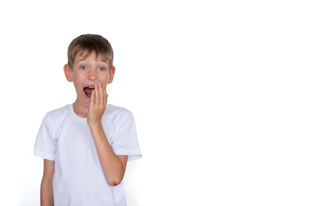 Verrast blond kind in een wit t-shirt geïsoleerd op een witte