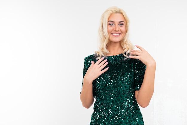 Verrast blond meisje in een groene elegante jurk met kopie ruimte