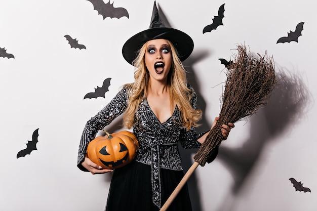 Verrast blond meisje schreeuwen op witte muur met vleermuizen. schitterende jonge heks die op vampierpartij koelen.