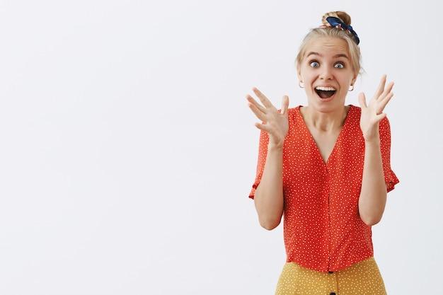 Verrast blond mooi meisje hoort fantastisch nieuws