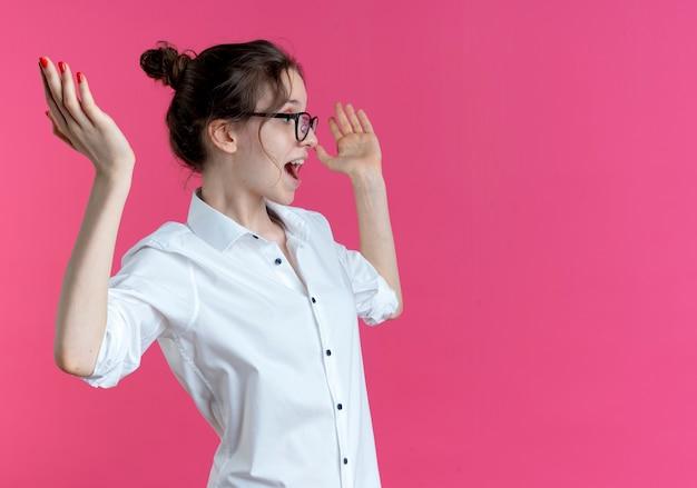 Verrast blond russisch meisje met bril staat zijwaarts met opgeheven handen