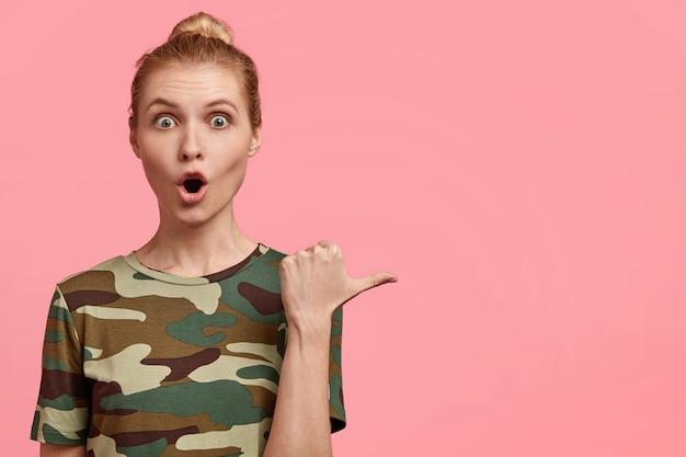 Verrast blonde jonge vrouw heeft geschokt doodsbange uitdrukking, opent mond wijd, wijst met duim, gekleed in camouflage t-shirt