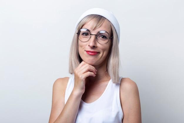 Verrast blonde jonge vrouw in glazen, witte hoed op een lichte achtergrond.