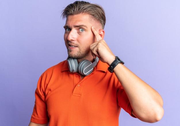 Verrast blonde knappe man met koptelefoon vinger op zijn tempel geïsoleerd op paarse muur met kopieerruimte
