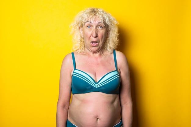 Verrast blonde oude vrouw in een zwembroek op een helder geel oppervlak