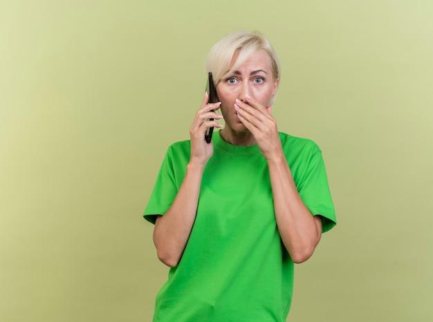 Verrast blonde slavische vrouw van middelbare leeftijd praten over telefoon kijken camera houden hand op mond geïsoleerd op olijfgroene achtergrond met kopie ruimte