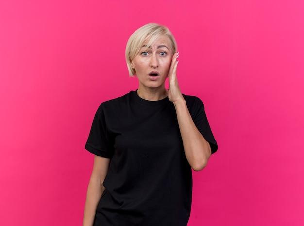 Verrast blonde slavische vrouw van middelbare leeftijd wat betreft hoofd dat op karmozijnrode muur met exemplaarruimte wordt geïsoleerd